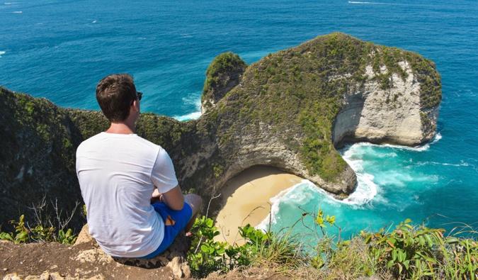 Sander from Ars Currendi sitting on a cliff near a beautiful beach