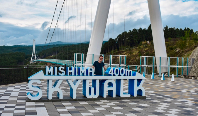 Sander from Ars Currendi posing for a photo neat the sign for a skywalk bridge